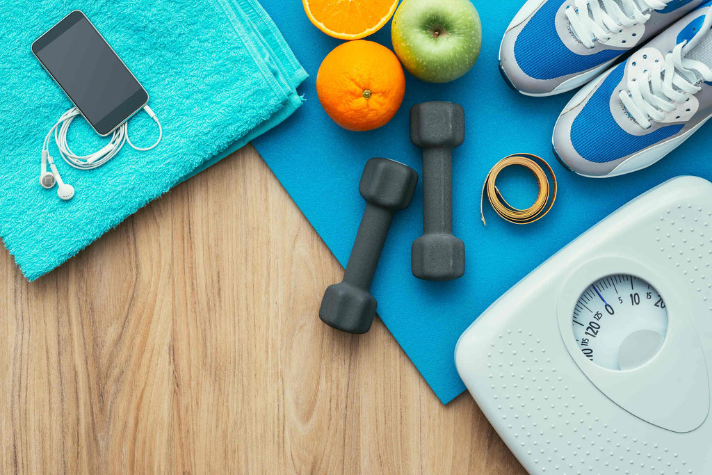 Sports-and-workout-equipment-on-a-wooden-floor-with-healthy-snacks