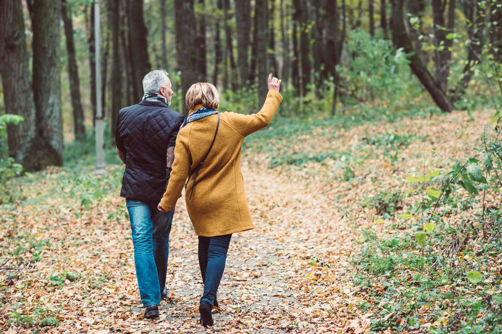 older couple walking in a forest