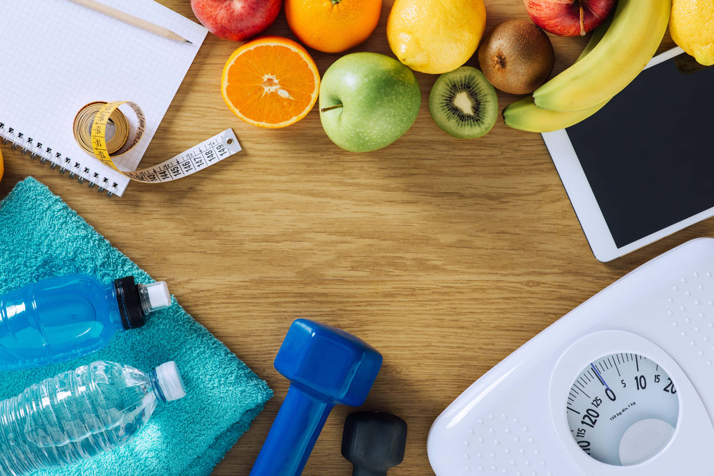water bottles, dumbells, weight scale, fruit, a notepad and pencil