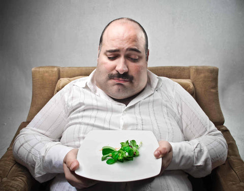 Sad man looking at his dish containing barely salad