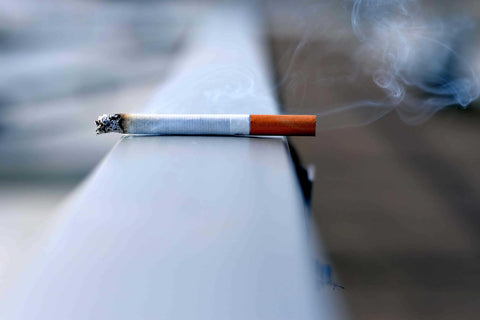 cigarette sitting on a railing