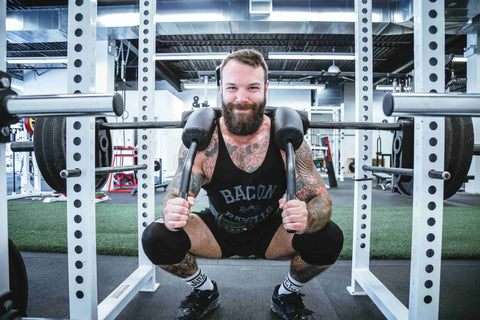 Man squatting a high amount of weight while smiling