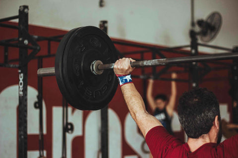 man lifting a barbell over his head