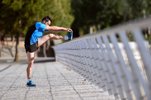 man stretching his leg on a bridge hand railing