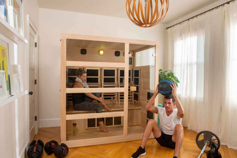man working out infront of a Tosi 4 Person Full Spectrum Infrared Sauna while a woman sits inside
