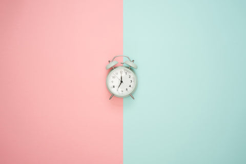 old fashion clock with a background of two colors, pink and light green