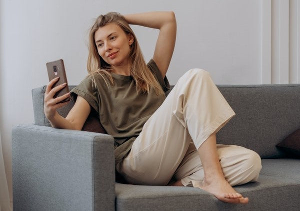 Woman sitting on gray couch using her smartphone