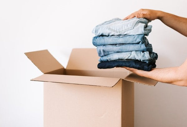 Person packing jeans into carton container