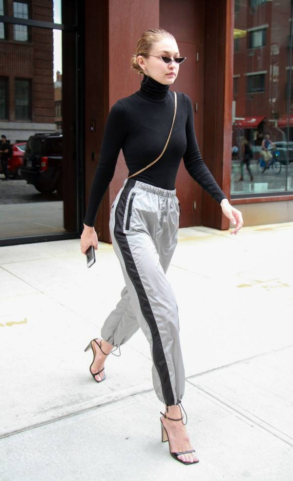 Woman in a black turtleneck and silver track pants walking