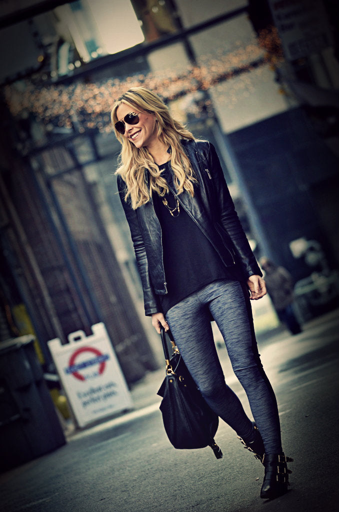 Woman in black leggings and leather jacket standing