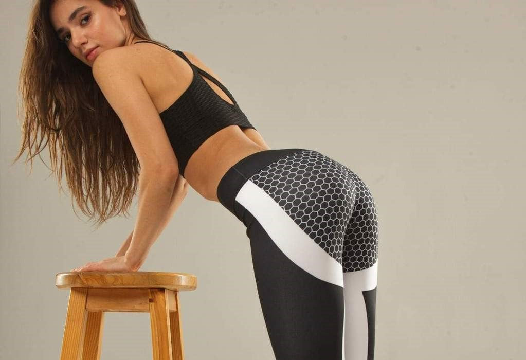 Woman in printed leggings props herself up with a wooden bench
