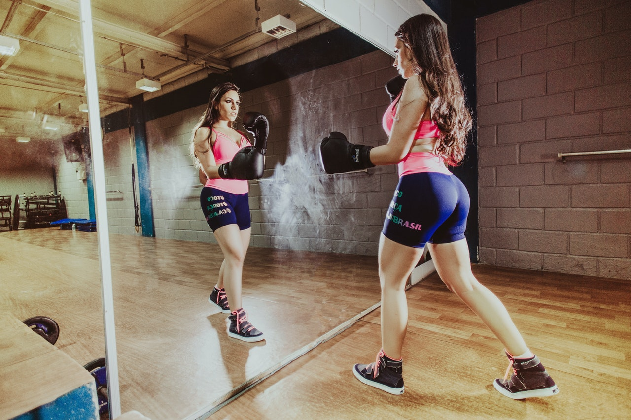 Sporty woman in boxing gloves punching air in gym