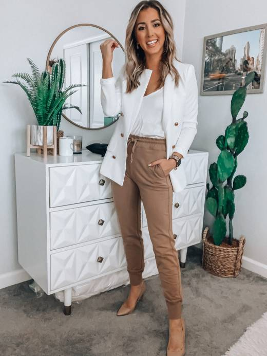 Woman in a white blazer and tan joggers posing