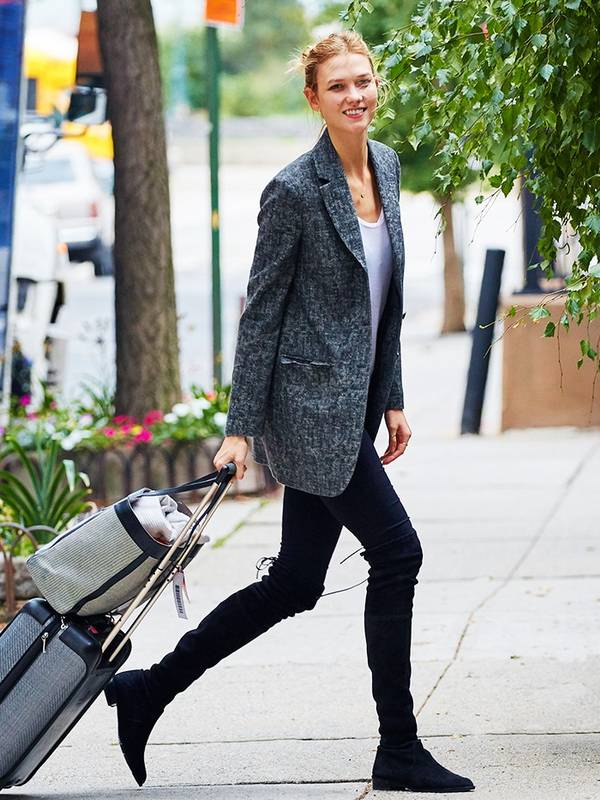 Woman in a blazer and black leggings towing luggage