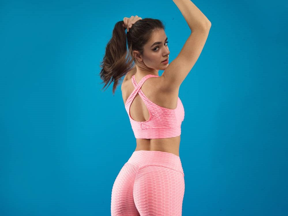 Woman in pink sportswear raises her right arm while looking back