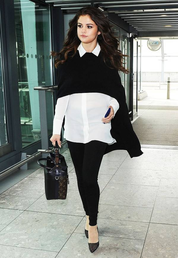Woman in a white shirt and black leggings walking