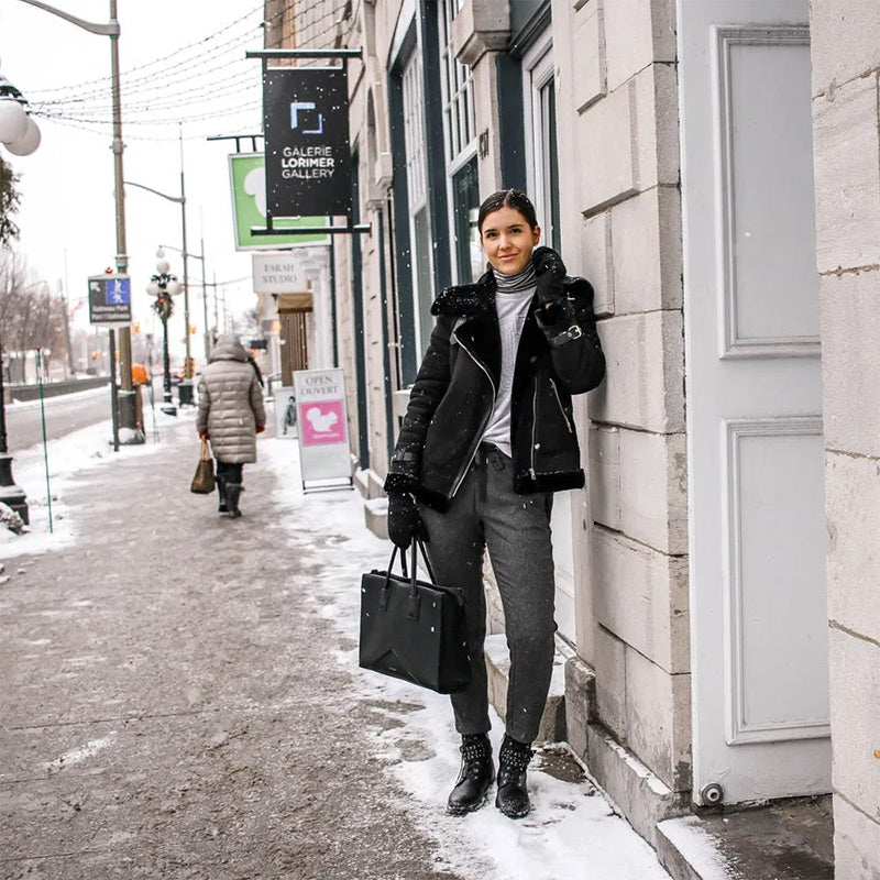 Woman in aviator jacket and sweatpants standing in the snow
