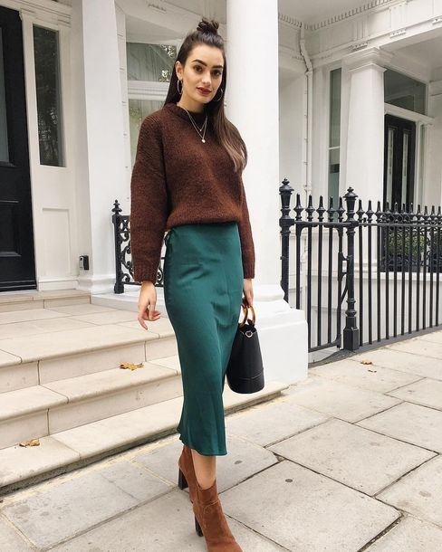 Woman in a green pencil skirt and brown sweater standing