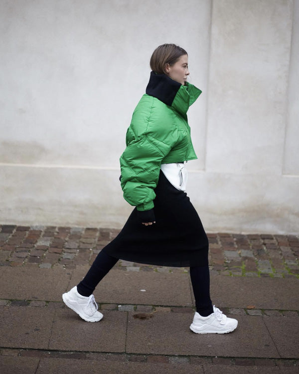 Woman in a green jacket and black dress walking on the pavement