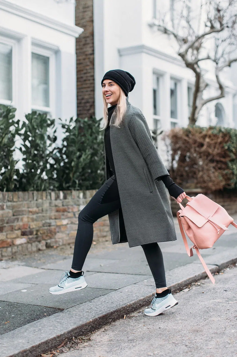 Woman in grey coat swinging a pink backpack