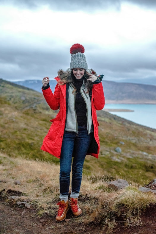 Woman in a red coat and jeans standing on a rocky surface
