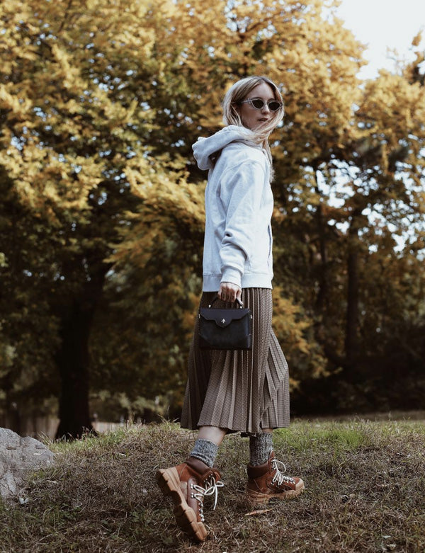 Woman in a hoodie and pleated skirt walking on the lawn