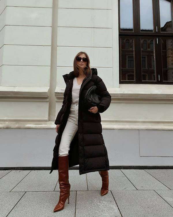 Woman in a puffer coat and brown boots walking on the pavement