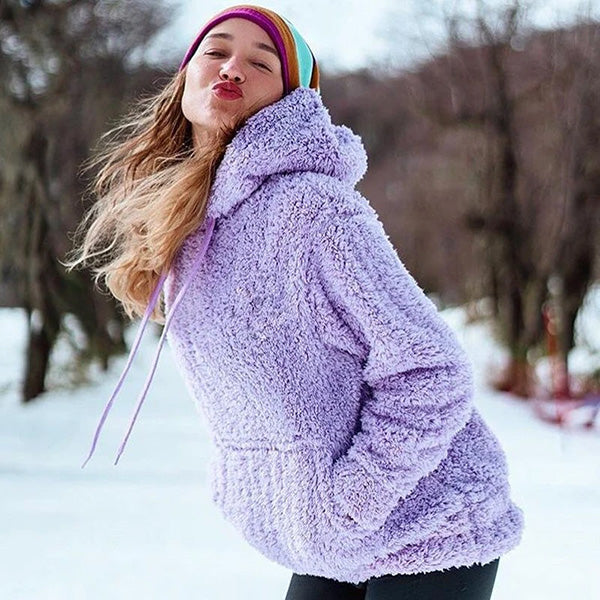 Woman in a purple fluffy hoodie standing in the snow