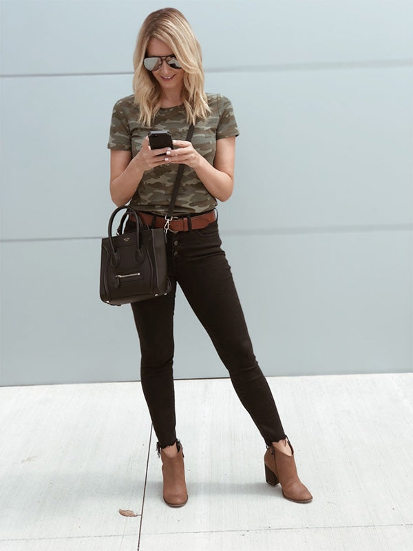 Woman in black jeans and camouflage t-shirt standing