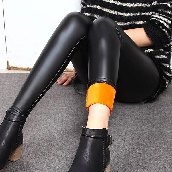 Woman in black leather leggings and booties sitting on the floor