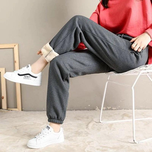 Woman in grey sweatpants and trainers sitting in a room