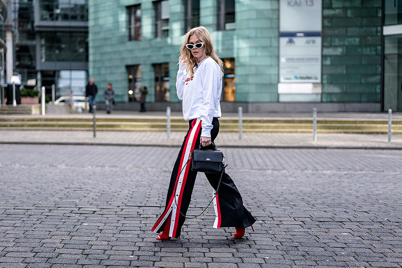 Woman in track pants and sweatshirt walking on the pavement