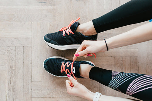 Woman with patterned leggings lacing up black trainers