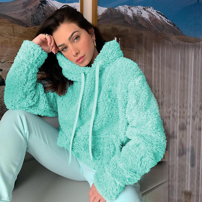 Woman in turquoise hoodie and pants sitting