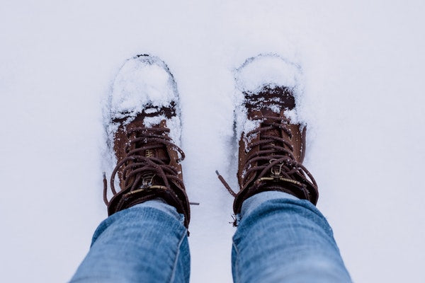 Person wearing brown boots and blue jeans standing in the snow