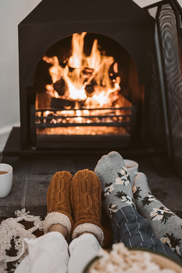 Two people in socks before the fireplace