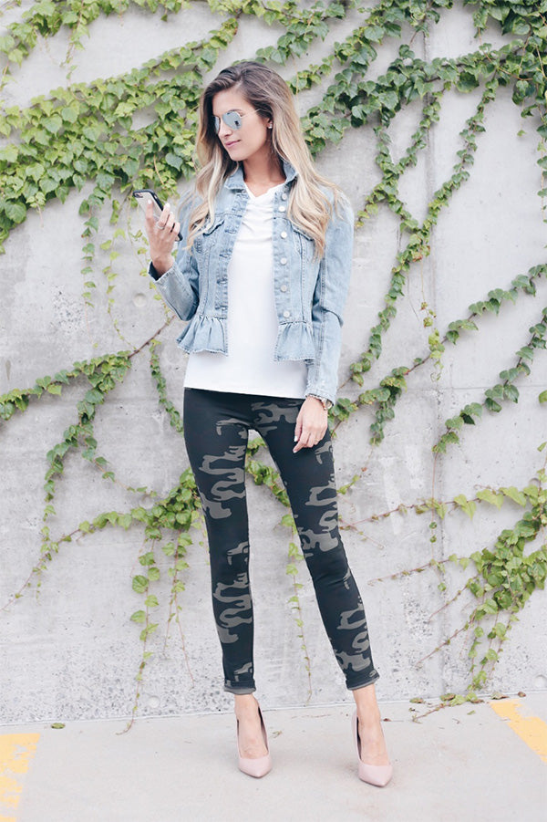 Woman in camouflage leggings and denim jacket standing