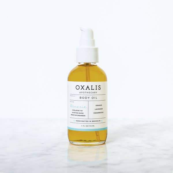 A glass bottle with spray pump for display.  Label reads Oxalis Apothecary Body Oil.