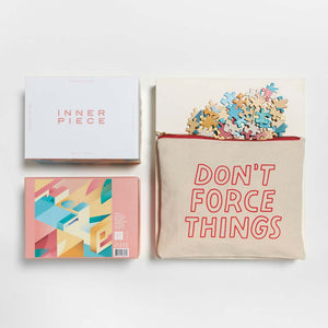 "A muslin pouch reads ""Don's Force Things"".  Puzzle pieces spill out of the pouch in bright colors.  Adjacent is the box that holds the puzzle for display reading ""Inner Piece"".  The puzzle is a geometric piece with abstract shapes."