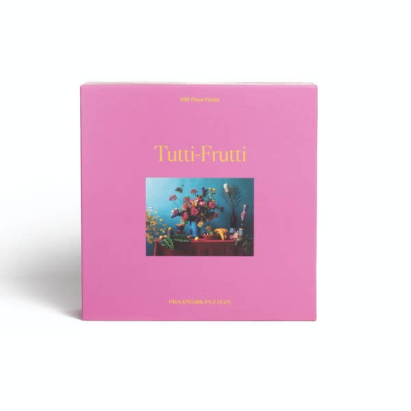 Display photo of the Tutti-Frutti puzzle. The box if a bright pink color with a photo of the completed puzzle on the front.  The puzzle features a photo of flowers and fruit on a table.