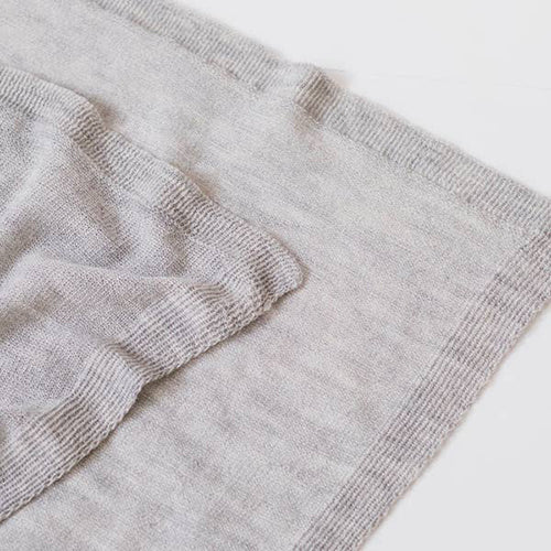 Close up view of a lightweight grey blanket wrap.