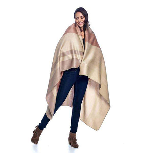 A woman is wrapped in a large alpaca throw showing the large size of the product.