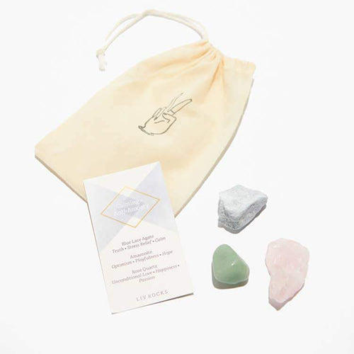 A small drawstring bag is displayed next to a set of three rocks and crystals.