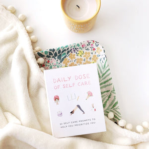 The self care daily dose of self care card deck sits on a cream colored blanket with an adjacent white candle.