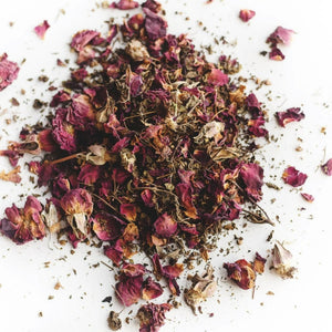 A pile of loose tea sits on a flat surface.  The tea has rose petals and a variety of dried herbs.