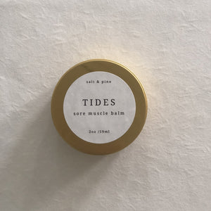 "A display photo of the gold tin with a label reading ""Tides Sore Muscle Balm""."