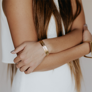 A woman with her arms crossed wears three gold cuff bangle bracelets