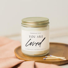 "Load image into Gallery viewer, A glass jar candle with gold lid sits on a wooden candle coaster with wooden matches.  The label reads ""You Are Loved""."