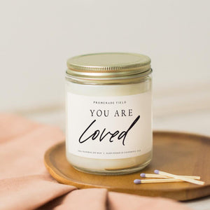 "A glass jar candle with gold lid sits on a wooden candle coaster with wooden matches.  The label reads ""You Are Loved""."