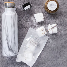 Load image into Gallery viewer, A photo of the Self-Care care package with them items laying on a grey fabric.  Items include a water bottle with a marble pattern, a black jar of lip balm, a gold tin that holds a candle, a shower steamers the spill onto the fabric.